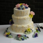 wedding cake with blue hydrangea, yellow daisy, pink roses