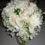 cascading bridal bouquet with white roses, calla lily, bouvardia, orchids