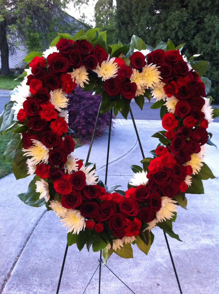 Memorial wreath with red roses, white spider mums and red carnations