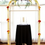 Wedding ceremony arch with swag of gerbera daisy, roses, snap dragons